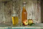 Flasche und Glas Apfelsaft, Äpfel (Jonagold) in einem rustikalen Schrankregal