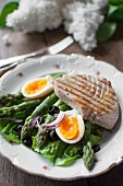 Salad Nicoise with lettuce, asparagus, egg, onions, black olives and tuna steak