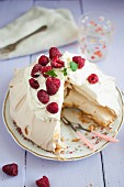 Pavlova (meringue cake) with mascarpone cream and fresh raspberries, sliced
