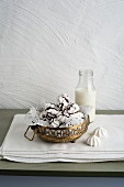 Meringues with chocolate glaze next to a bottle of milk