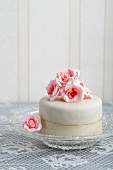 A mini tartlet with ready-roll icing decorated with sugar roses