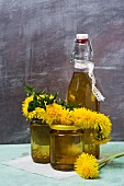 Dandelion syrup in a fliptop bottle with jars of dandelion honey