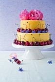A two tier fondant cake decorated with flowers and cherries