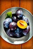 Fresh plums on a pewter plate
