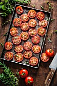 Halved tomatoes for drying on a baking tray