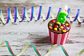 A birthday muffin decorated with chocolate lentils and candles