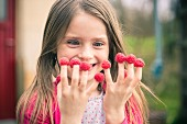 A grinning little girl with raspberries on her fingers