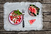 Watermelon salad with feta cheese, mint and sesame seeds on a wooden table