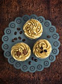Three cupcakes decorated with coffee cream
