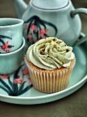 A cupcake with pistachio cream and a tea service