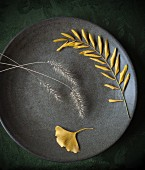 Yellow autumnal leaves and grasses on a plate