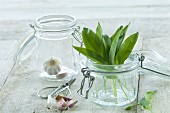 Fresh wild garlic and bulbs of garlic in a flip-top jar