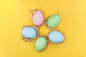 Colourful Easter eggs with white dots on a yellow surface
