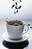 Coffee beans falling into a white coffee cup