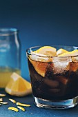 A Cuba Libre with ice cubes and lemon wedges