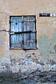 Geschlossener Fensterladen mit Herzmotiv in altem Gemäuer mit Hausnummer