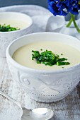 Potato soup with green asparagus and chives in ceramic bowls
