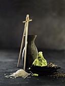 Rohe Reiskörner, Wasabipaste und zweifarbiger Sesam auf kleinen Schieferplatten, Essstäbchenpaar an Keramikkaraffe gelehnt