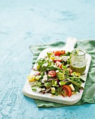 A summer salad with a herb vinaigrette on a chopping board