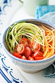 Healthy low fat salad of courgette and carrot spaghetti with cherry tomatoes