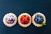 Three short crust fruit tartlets with raspberries, strawberries and blueberries