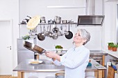 A middle aged woman in a kitchen tossing a pancake