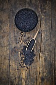 Black, uncooked, organic basmati rice in a bowl and on a spoon (seen from above)