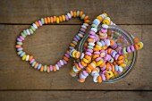 A colourful candy necklace in a jar on a wooden surface (seen from above)