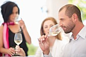 A wine tasting session: a young man sniffing a glass of white wine