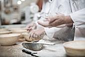Bäcker beim Ausmehlen von Brotbackformen aus Peddigrohr