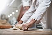 Bäcker bei der Brotherstellung: Ausrollen des Teiges mit Nudelholz
