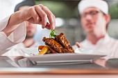 Koch in Restaurantküche garniert Fleischgericht mit Kräutern