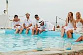 Hochzeitsgäste in sommerlicher Kleidung am Poolrand sitzend