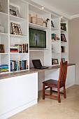 Arbeitsplatz mit Laptop an offenem weißem Regal mit Fernseher in zeitgenössischem Ambiente