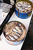 Salted sardines in metal tins at a fish market