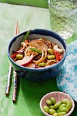 Noodles with beans, peppers, plums and cashew nuts in a soy dressing