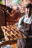 Junger Konditor mit frischen Croissants auf einem Backblech