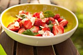 A strawberry salad with flaked almonds and basil