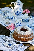 A Bundt cake on a table laid for coffee in the garden
