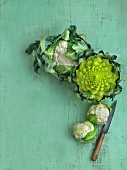 Cauliflower and Romanesco broccoli on a green wooden surface