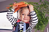 A little girl with fresh carrots