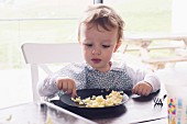 A little boy eating pasta