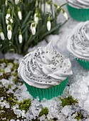 Cupcakes decorated with white frosting and silver pearls in fake snow