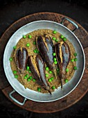 Stuffed aubergines with peas on a lentil purée