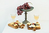 Small wooden boards with crackers, Brie, Danish caraway cheese, blue cheese, mini crostini, walnuts, fix, blueberries, grapes and Federweisser (a cloudy beverage in the process of fermenting, somewhere in between must and wine)