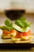 Crackers cheese, tomatoes and avocado served with red wine