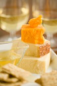 A cheese platter with honey and crackers served with white wine