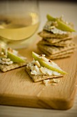 Crackers topped with soft cheese, care and almonds
