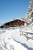 Verschneite Berghütte unter blauem Himmel