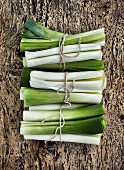 Bundles of leeks on a rustic wooden surface